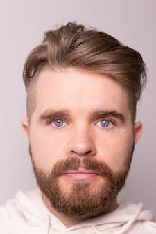 Portret młodego mężczyzny z brodą i wąsami oraz modną fryzurą nosi luźną bluzę z kapturem ma poważne