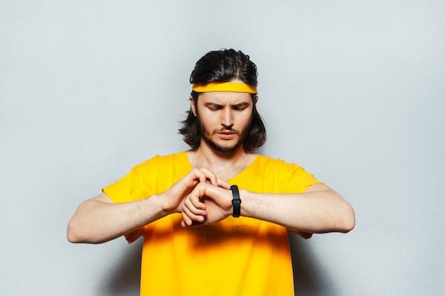 Portret młodego mężczyzny z długimi włosami na sobie żółtą koszulę za pomocą smartwatcha.