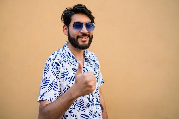 Portret młodego mężczyzny z letnich ubrań i kciuki do góry przeciwko żółtej przestrzeni.