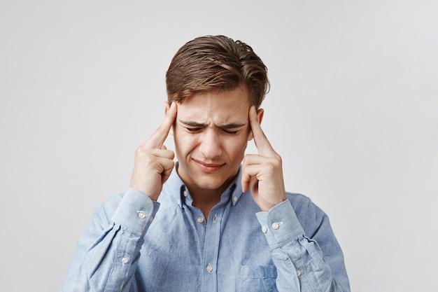 Portret młodego mężczyzny z okropnym bólem głowy.