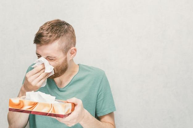 Portret młodego mężczyzny z pudełkiem papierowych serwetek
