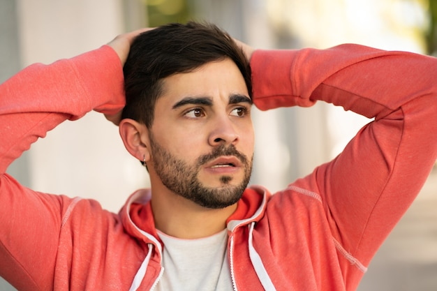 Portret młodego mężczyzny zestresowany i martwi się o coś stojąc na zewnątrz. koncepcja miejska.
