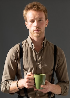 Portret młodego modelu mężczyzna trzyma filiżankę kawy