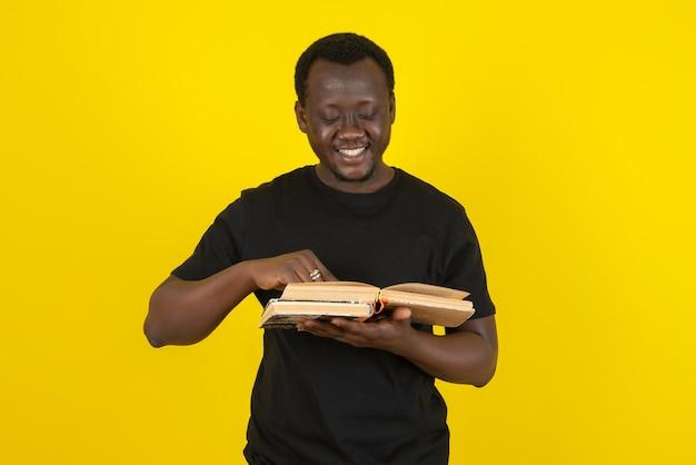 Portret młodego modelu mężczyzny czytającego książkę na tle żółtej ściany