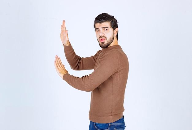 Portret młodego modelu mężczyzny stojącego i pchającego wyimaginowany obiekt. zdjęcie wysokiej jakości
