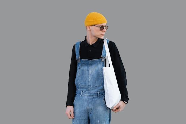 Portret młodego modnego mężczyzny patrzącego przez ramię, niosącego torbę na zakupy wielokrotnego użytku