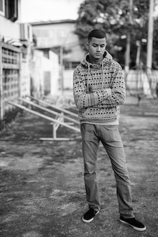 Portret młodego multi etnicznego azjatyckiego mężczyzny na ulicach na zewnątrz w czerni i bieli