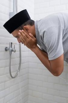 Portret młodego muzułmanina wykonuje ablucję (wudhu) przed modlitwą w domu