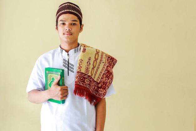Portret młodego muzułmanina z azji, trzymającego świętą księgę alquran i matę modlitewną na ramieniu, przygotowują się do modlitwy