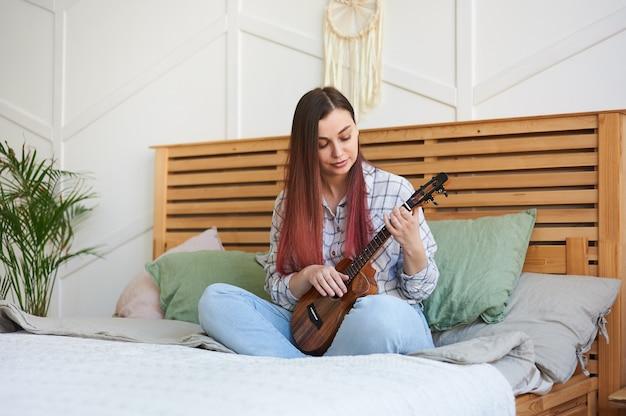 Portret młodego muzyka grającego na ukulele, siedzącego na łóżku w swoim domu, ze skrzyżowanymi nogami.