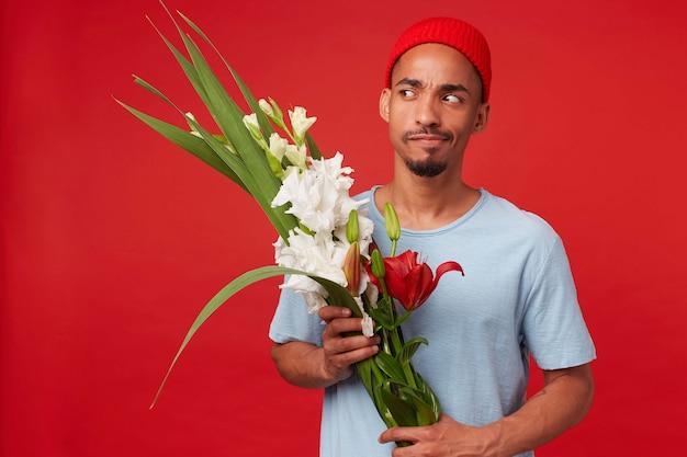Portret młodego myślącego atrakcyjnego mężczyzny w czerwonym kapeluszu i niebieskiej koszulce, trzyma bukiet w dłoniach, wątpi i odwraca wzrok, stoi na czerwonym tle.