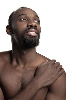 Portret młodego nagiego szczęśliwego uśmiechniętego afrykańskiego mężczyzny w studio.