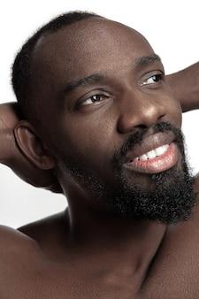 Portret młodego nagiego szczęśliwego uśmiechniętego mężczyzny w studio