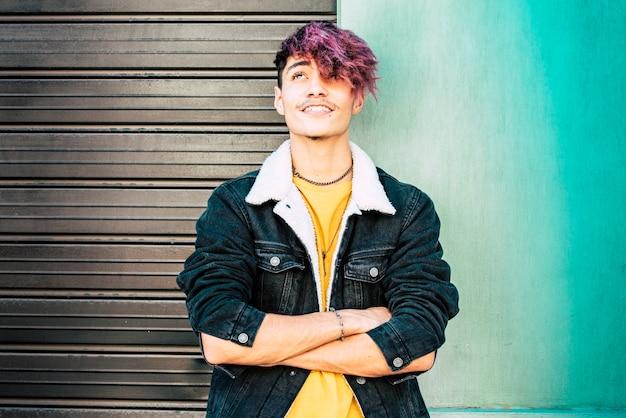 Portret młodego nastolatka alternatywnego chłopca i kolorowe ubrania i tło ścienne miejskie
