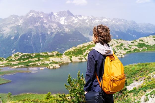 Portret młodego nastolatka z żółtym plecakiem w czarnej kurtce, stojącego w górach we francuskich alpach, z przyjemnością odwracającego wzrok w kierunku jeziora. atrakcje turystyczne w lecie.