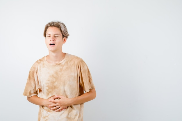 Portret młodego nastoletniego chłopca cierpiącego na ból brzucha w koszulce i patrzącego na zmartwiony widok z przodu