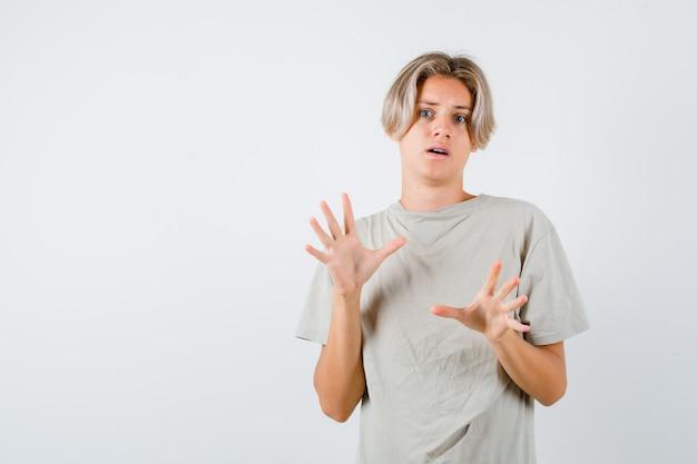 Portret młodego nastoletniego chłopca, który próbuje zablokować się rękami w koszulce i wygląda na przestraszonego widoku z przodu