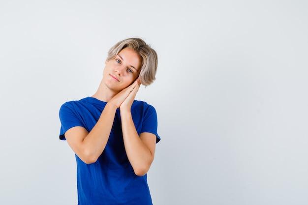 Portret młodego nastoletniego chłopca opartego na dłoniach jako poduszki w niebieskiej koszulce i patrzącego z nadzieją na widok z przodu