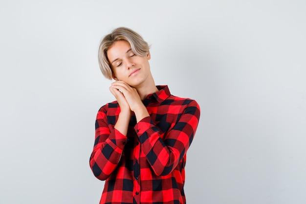 Portret młodego nastoletniego chłopca opierając się na dłoniach jako poduszce w kraciastej koszuli i patrząc na senny widok z przodu