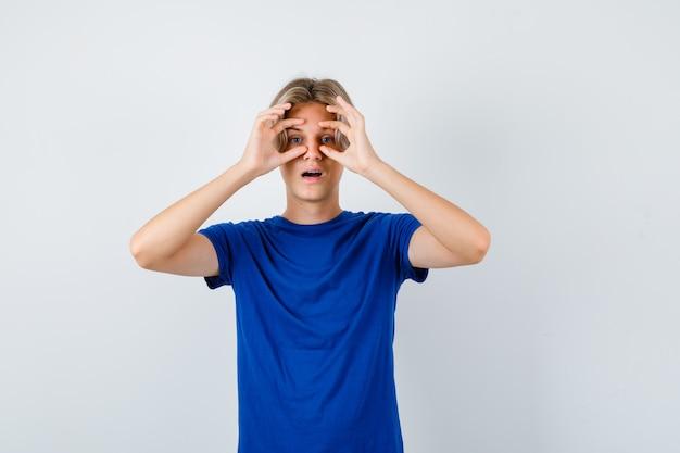 Portret młodego nastoletniego chłopca patrzącego przez palce w niebieskiej koszulce i patrzącego zdumiony widok z przodu