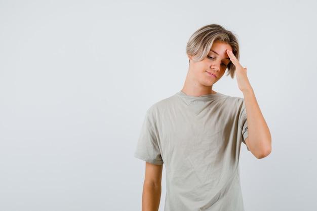 Portret młodego nastoletniego chłopca pocierającego czoło