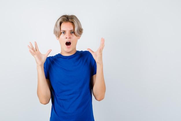 Portret młodego nastoletniego chłopca podnoszącego ręce, krzyczącego w niebieskiej koszulce i przerażonego widoku z przodu