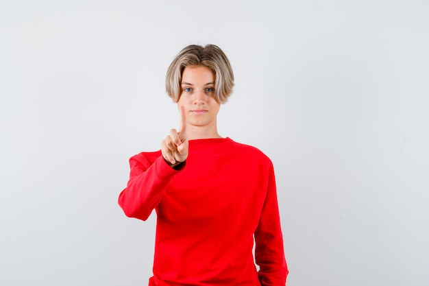 Portret młodego nastoletniego chłopca pokazującego chwyt minutowy w czerwonym swetrze i patrzącego pewnie z przodu