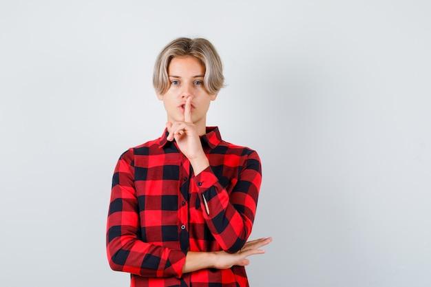 Portret młodego nastoletniego chłopca pokazującego gest ciszy w kraciastej koszuli i patrzący na ostrożny widok z przodu