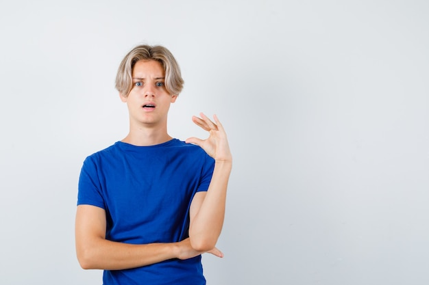 Portret młodego nastoletniego chłopca pokazującego mały znak w niebieskiej koszulce i patrzącego zszokowany widok z przodu