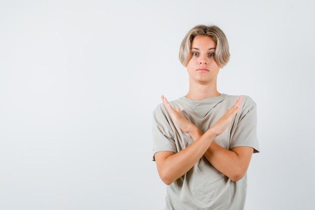 Portret młodego nastoletniego chłopca pokazujący gest odmowy w koszulce i patrzący przestraszony widok z przodu