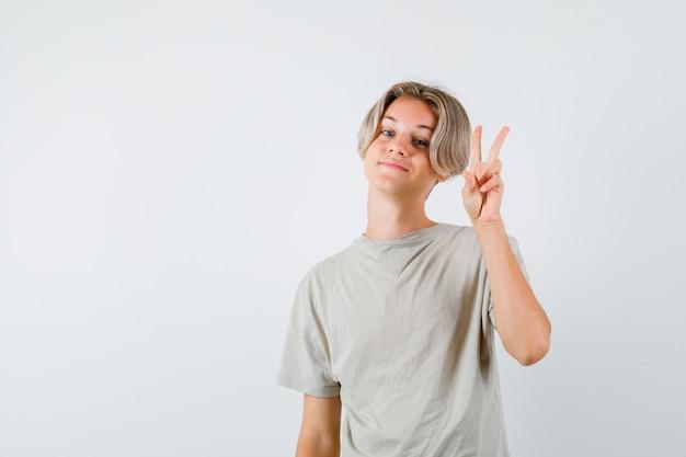 Portret młodego nastoletniego chłopca pokazujący gest pokoju w koszulce i patrzący wesoły widok z przodu