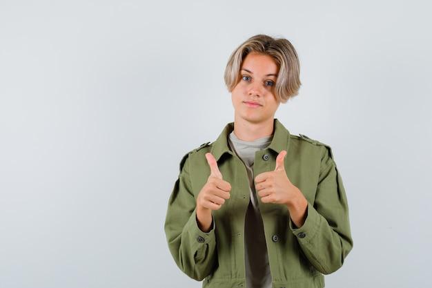 Portret młodego nastoletniego chłopca pokazujący podwójne kciuki w t-shirt, kurtkę i pewny siebie widok z przodu