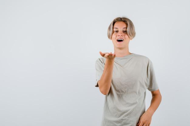 Portret młodego nastoletniego chłopca rozciągającego rękę na aparat w t-shirt i patrzący szczęśliwy widok z przodu