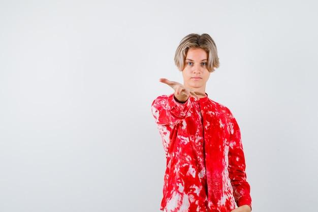 Portret młodego nastoletniego chłopca rozciągającego rękę w aparacie w koszuli i patrzącego pewnie z przodu
