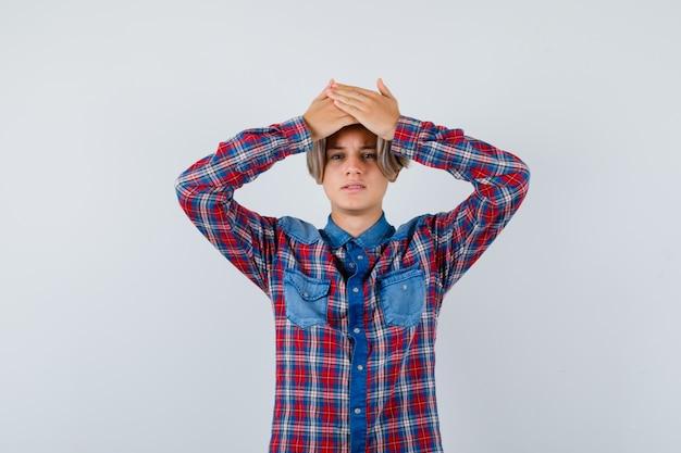 Portret młodego nastoletniego chłopca trzymającego ręce na głowie w kraciastej koszuli i patrzącego na zapominalski widok z przodu