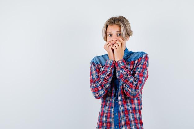 Portret młodego nastoletniego chłopca trzymającego ręce na ustach w kraciastej koszuli i wyglądającego na przerażonego widoku z przodu