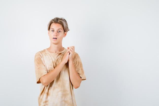 Portret młodego nastoletniego chłopca trzymającego ręce splecione w t-shirt i patrzącego na zdziwionego widok z przodu