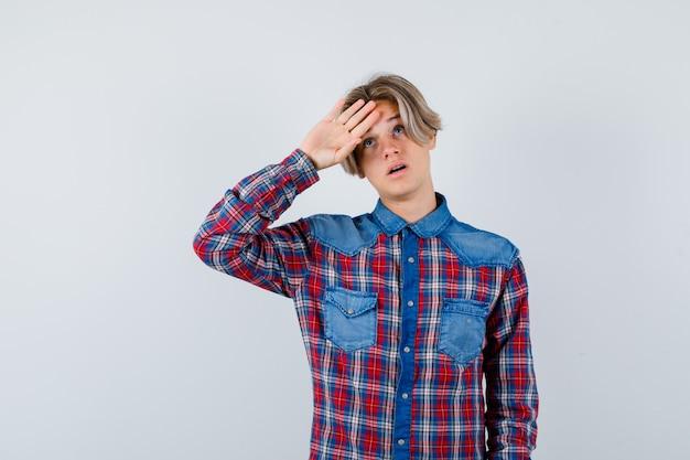 Portret młodego nastoletniego chłopca trzymającego rękę na czole w kraciastej koszuli i patrzącego na przemyślany widok z przodu