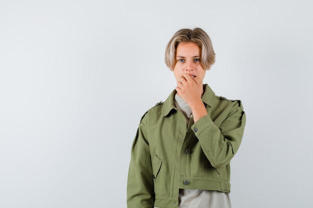 Portret młodego nastoletniego chłopca trzymającego rękę na ustach w koszulce, kurtce i patrzącym na niespokojny widok z przodu