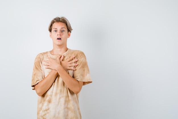 Portret młodego nastoletniego chłopca trzymającego skrzyżowane ręce na piersi w koszulce i patrzącego na przestraszonego widoku z przodu