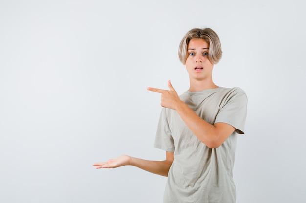 Portret młodego nastoletniego chłopca wskazującego w lewo