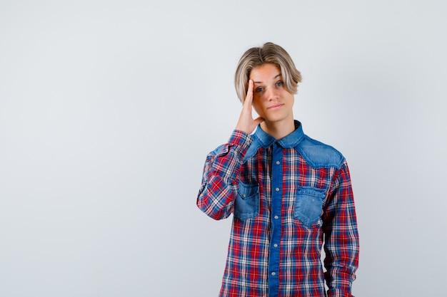 Portret młodego nastoletniego chłopca z ręką na boku twarzy w kraciastej koszuli i patrzący na inteligentny widok z przodu