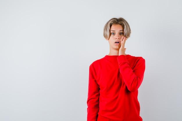 Portret młodego nastoletniego chłopca z ręką na policzku w czerwonym swetrze i patrząc zdziwionym widokiem z przodu