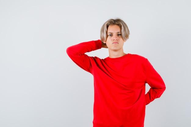 Portret młodego nastoletniego chłopca z ręką za głową w czerwonym swetrze i patrzącym zaniepokojonym widokiem z przodu