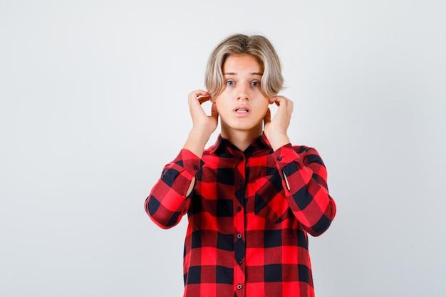 Portret młodego nastoletniego chłopca z rękami w pobliżu uszu w kraciastej koszuli i patrzącym zdziwionym widokiem z przodu