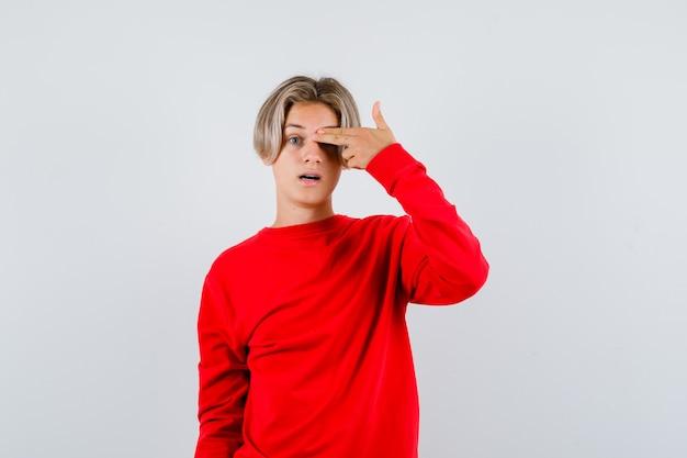 Portret młodego nastoletniego chłopca zakrywającego oko palcami w geście pistoletu w czerwonym swetrze i patrzącego na zdziwionego widok z przodu