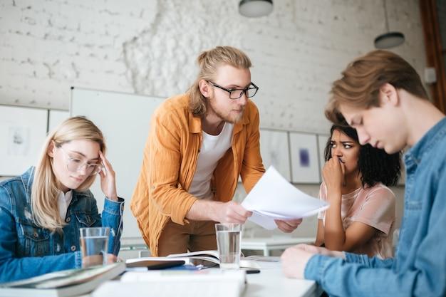 Portret młodego nauczyciela w okularach, opierając się na stole i wyjaśniając coś uczniom z testami w rękach