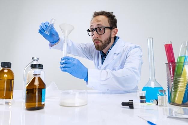 Portret młodego naukowca, chemika lub lekarza prowadzi badania chemiczne w laboratorium farmaceutycznym.