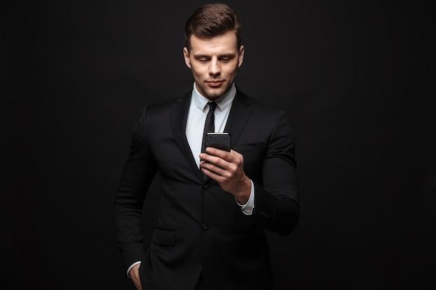 Portret młodego nieogolonego biznesmena ubranego w formalny garnitur za pomocą telefonu komórkowego odizolowanego na czarnej ścianie