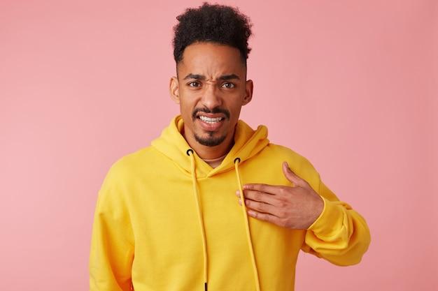 Portret młodego niezadowolonego afroamerykanina w żółtej bluzie z kapturem, wskazuje na siebie w niezrozumieniu tego, co się dzieje, patrząc.